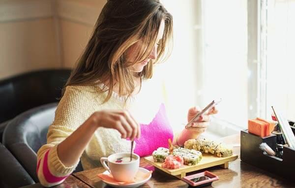 スマホをいじりながら食事をする女性